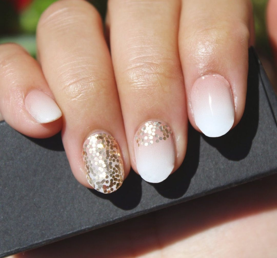 Short white ombre nails with gold glitter