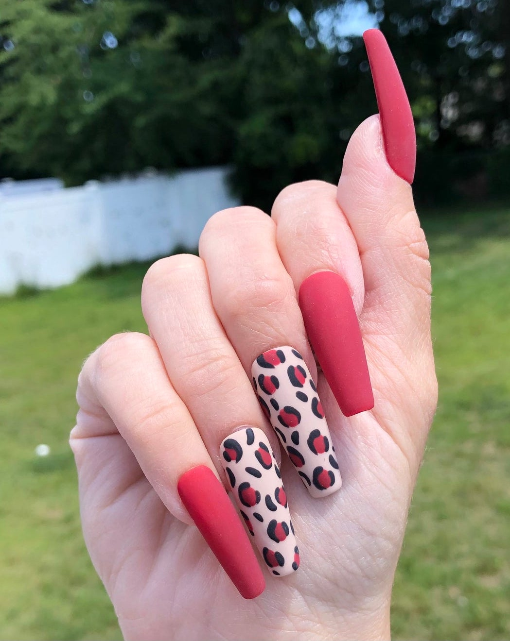 Soft red matte nails with leopard print nail art