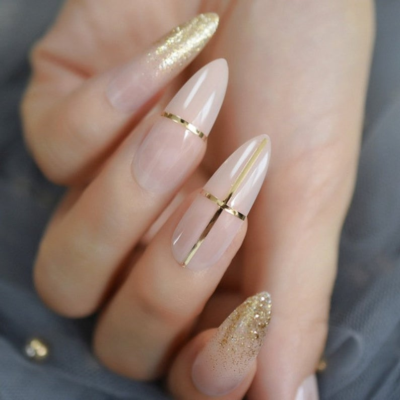 Soft pink stiletto nails with gold accents