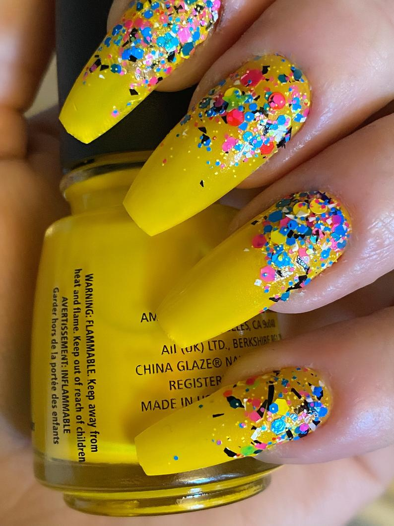 Yellow nails topped with colorful chunky glitter