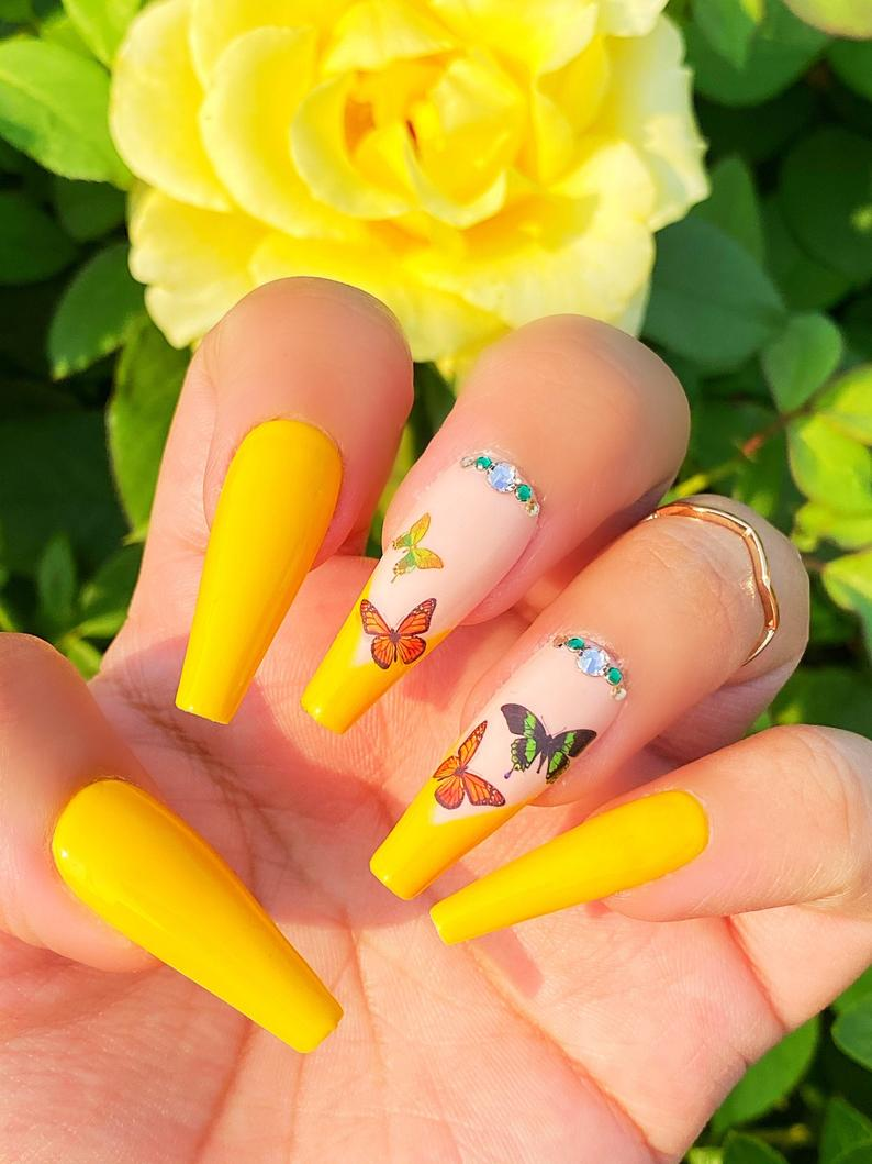 Bright yellow nails with butterflies