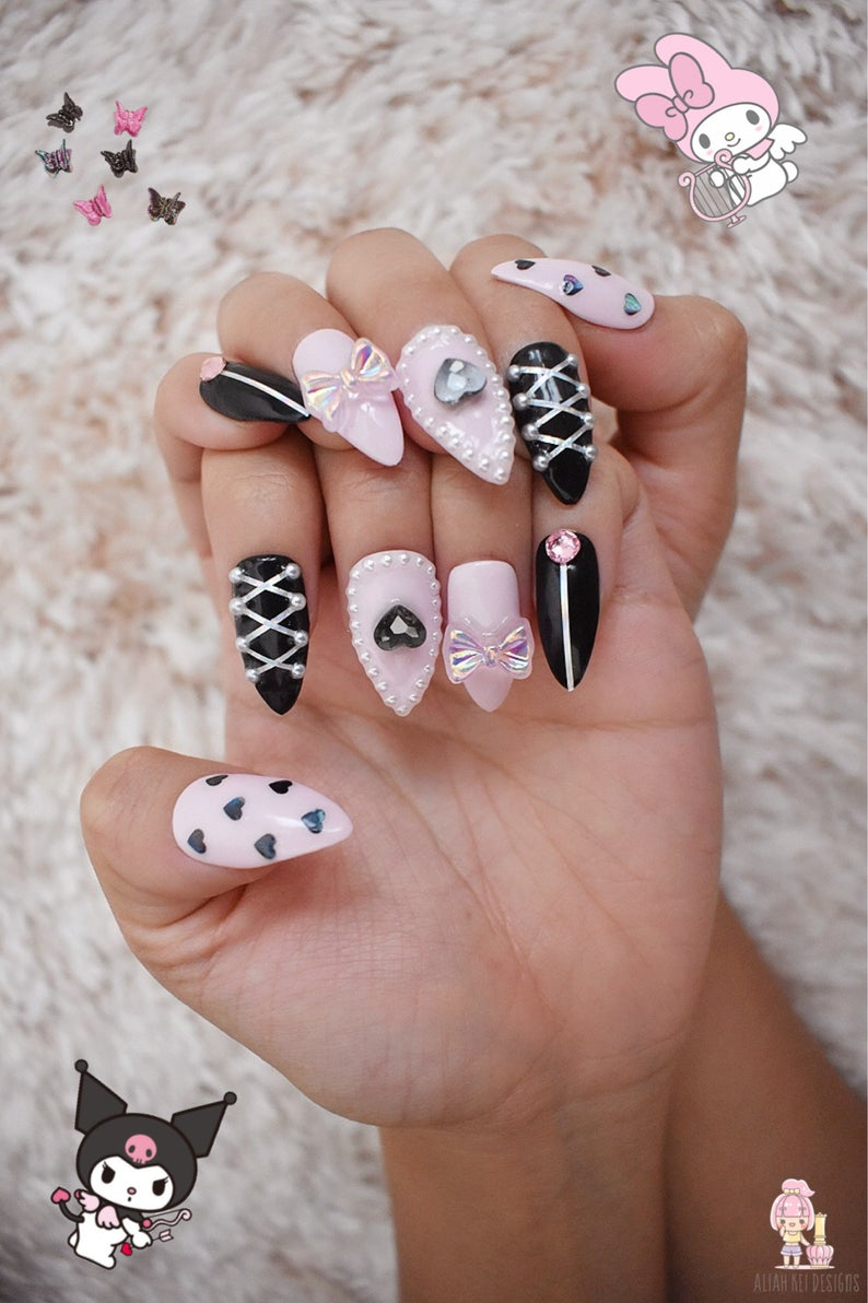 Pink and black kawaii nail art with embellishments