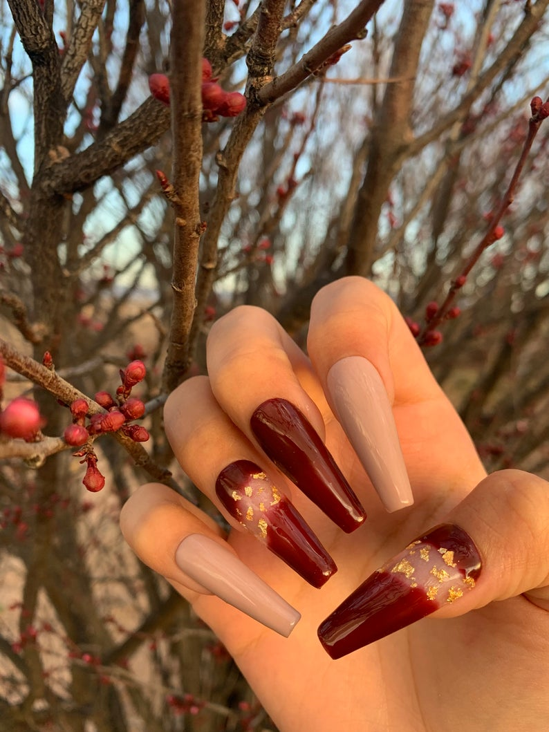 Nude and burgundy nails with gold flakes