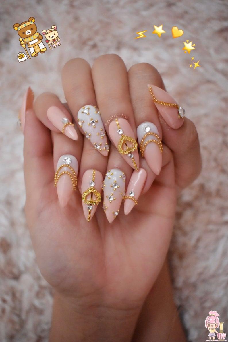 Soft pink kawaii nail art with gold embellishments