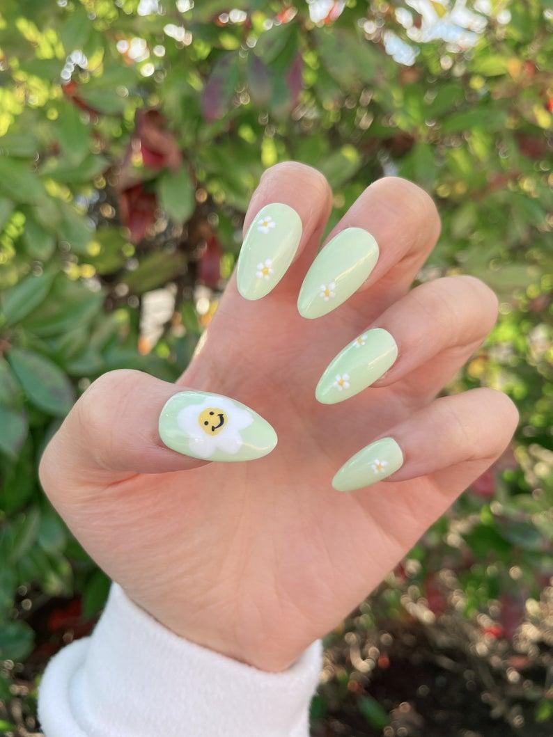Light green nail art with daisies