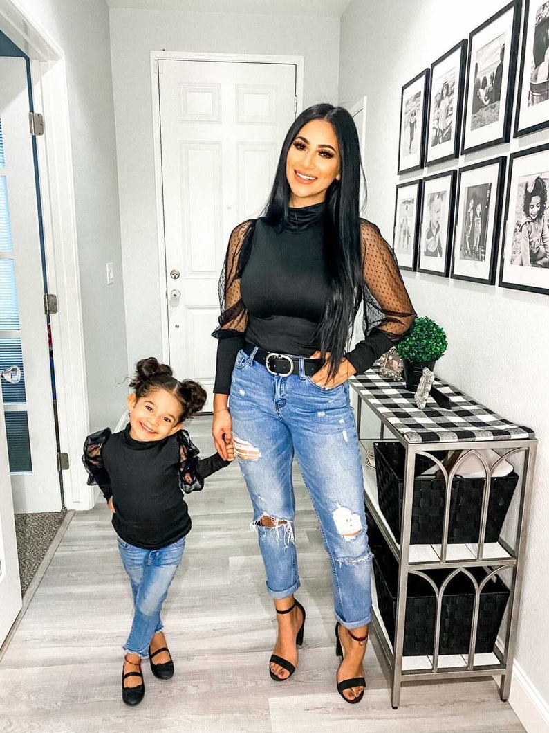 Matching black mesh blouse and jeans for mom and daughter