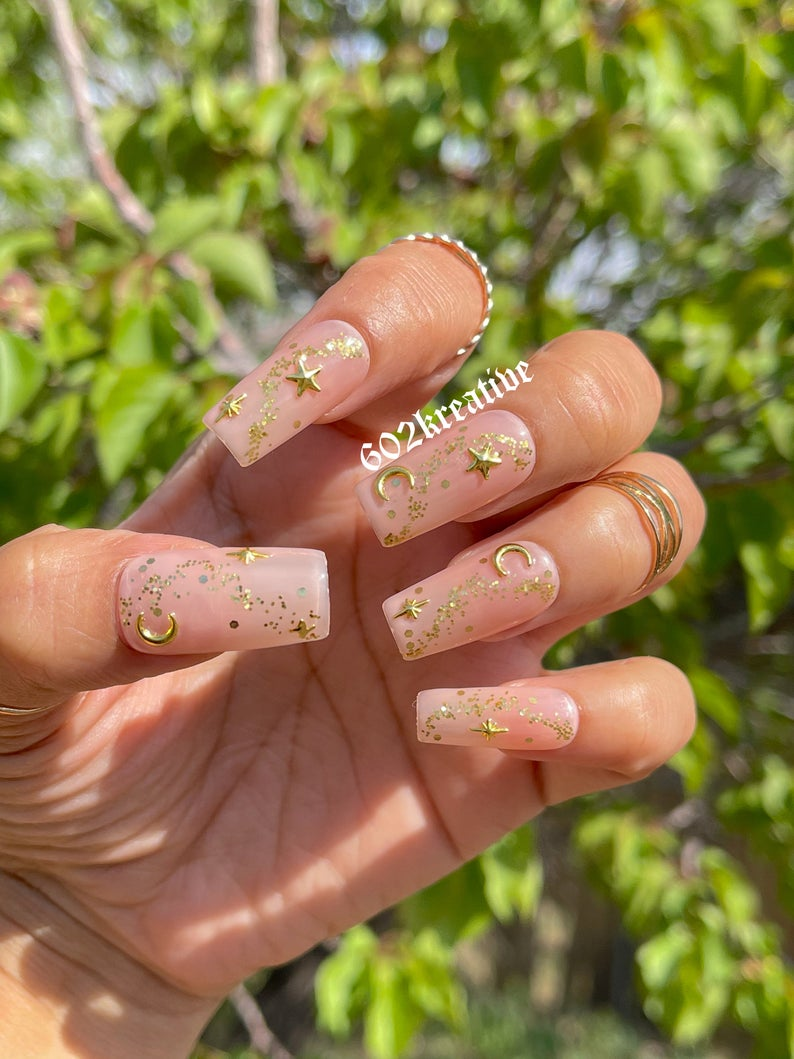 Nude nails with gold sparkles and stars