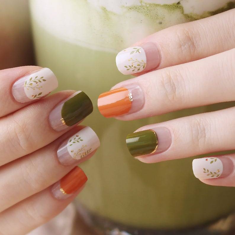 Olive green and orange gel nails with floral details