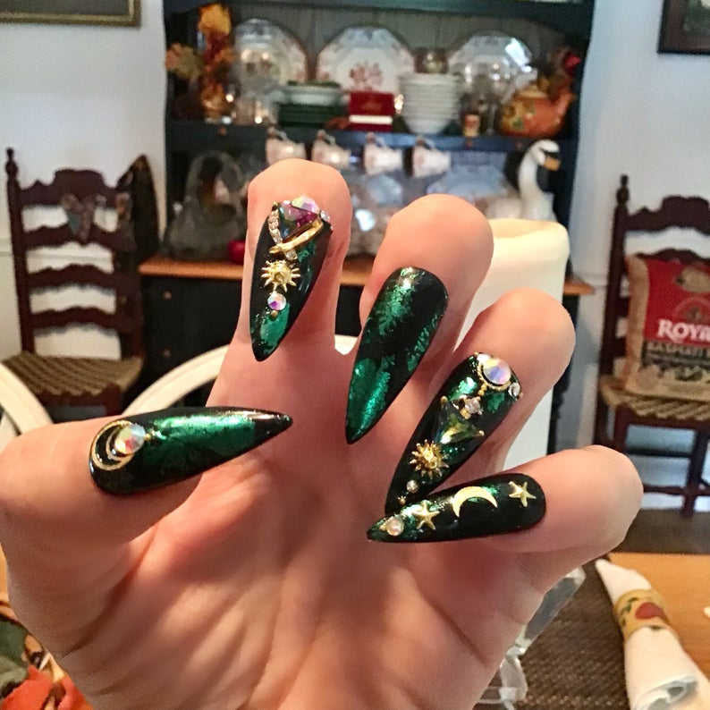 Stiletto nails with green accents and sun, moon and stars