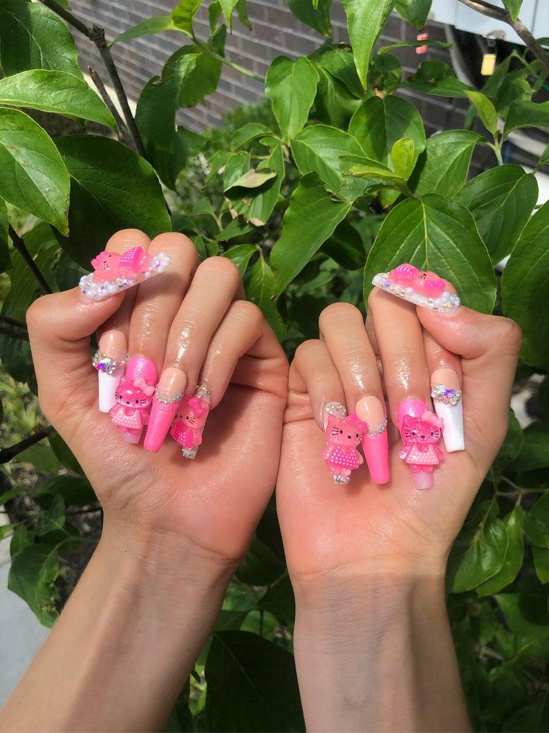 Hot pink kawaii nails with Hello Kitty nail art embellishments