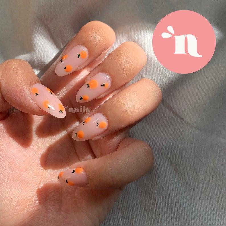 Nude gel nails with orange fruit details