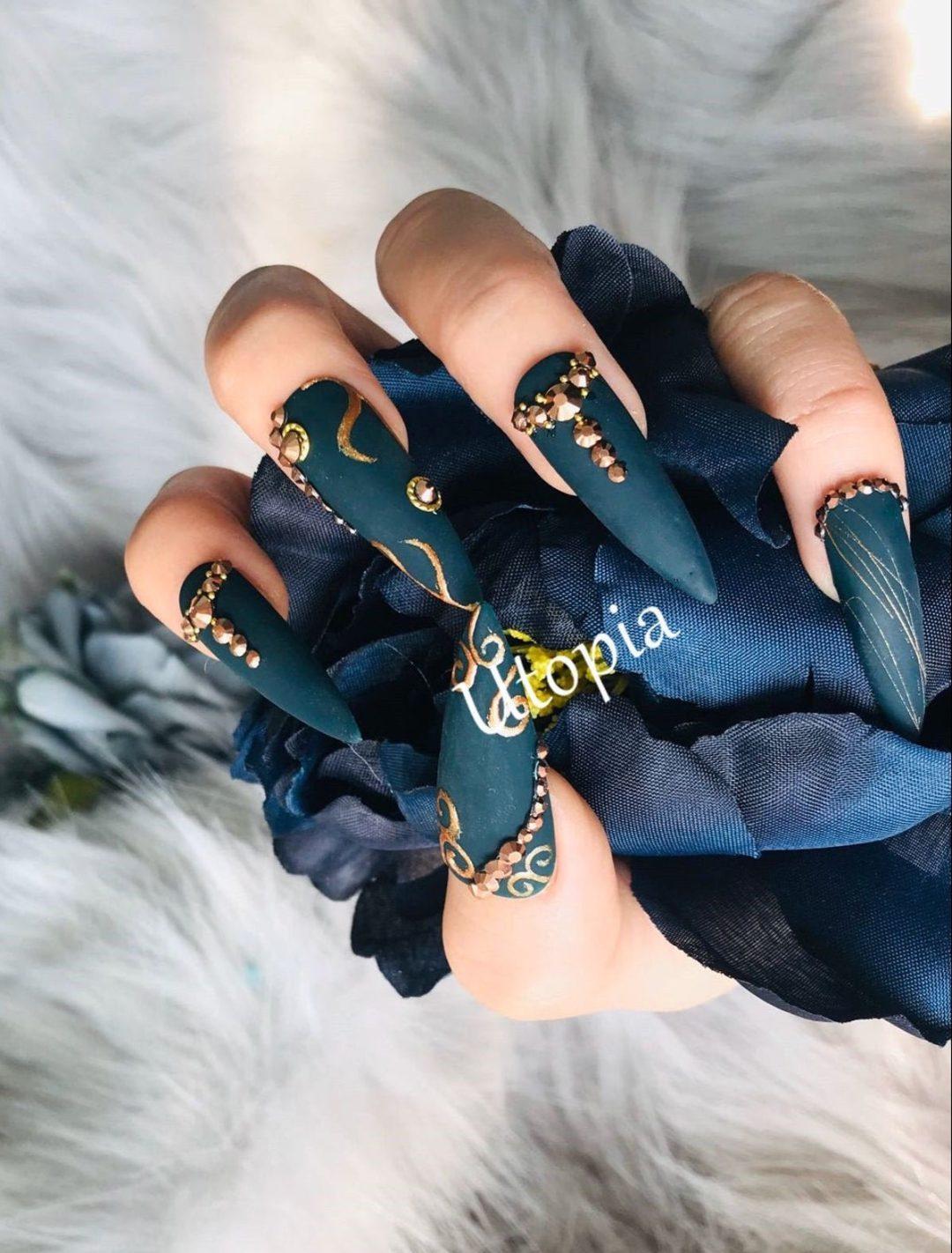 Matte dark blue nails with gold rhinestones