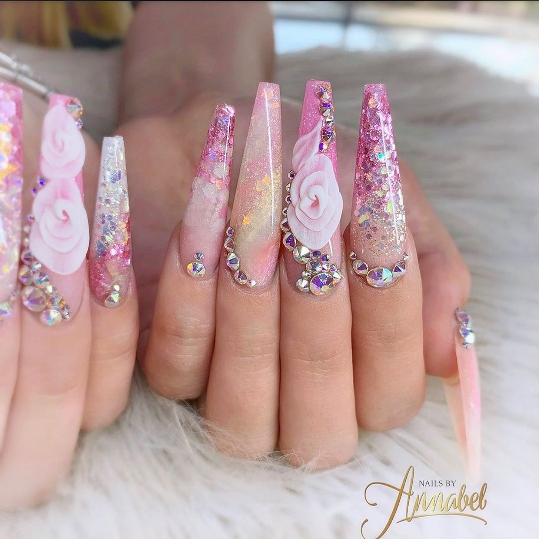 Pink nails with holographic glitter and flower decals with rhinestones