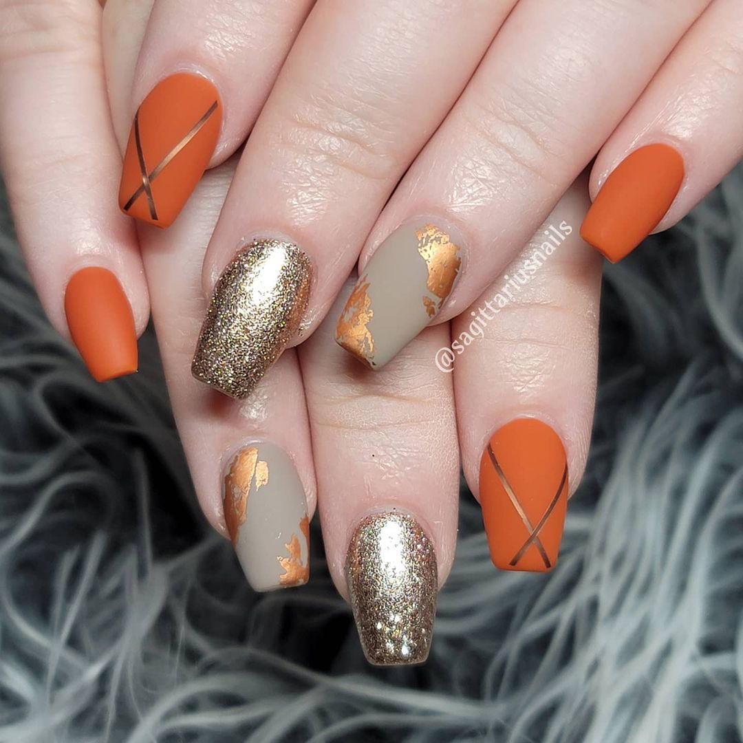 Matte burnt orange nails with grey and gold designs