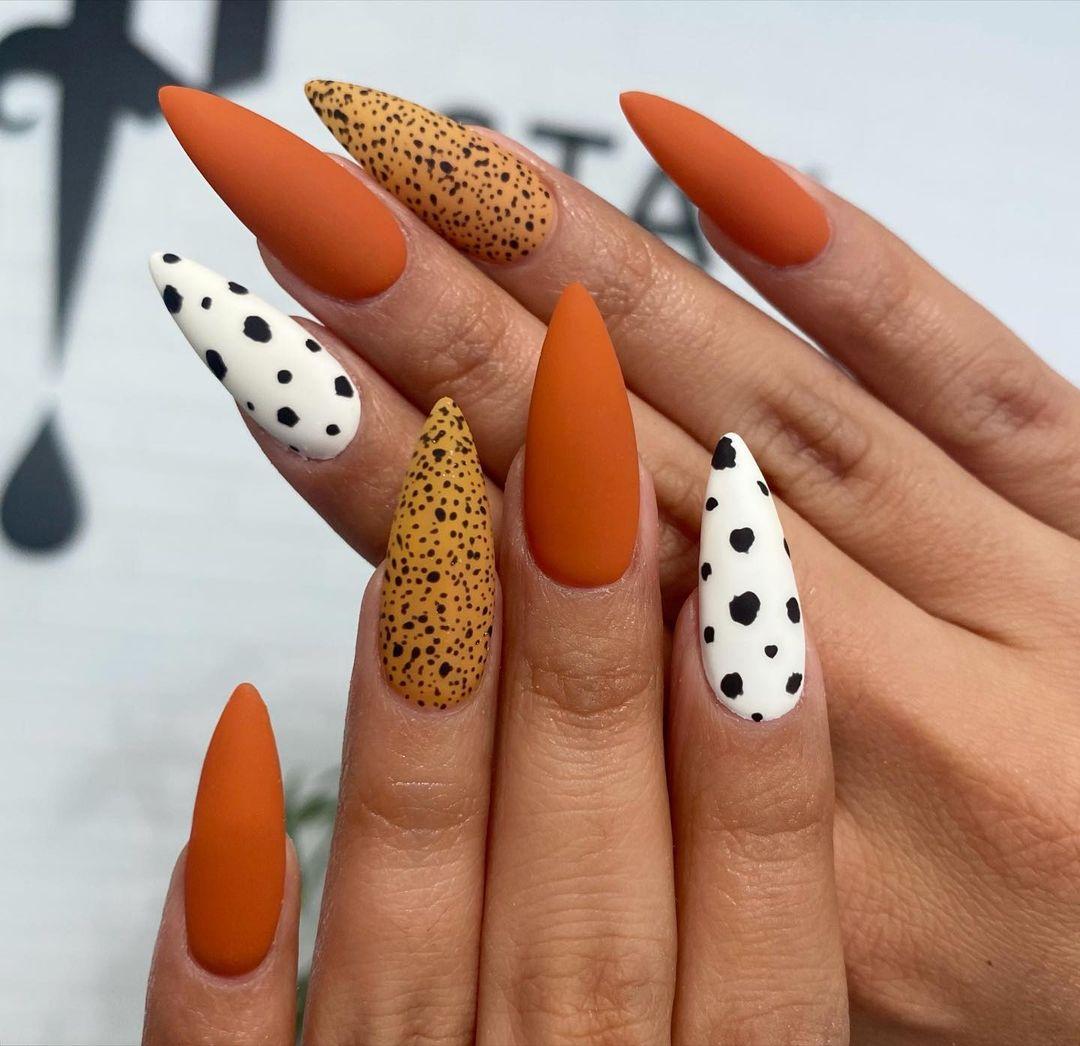 Matte burnt orange nails with cow print