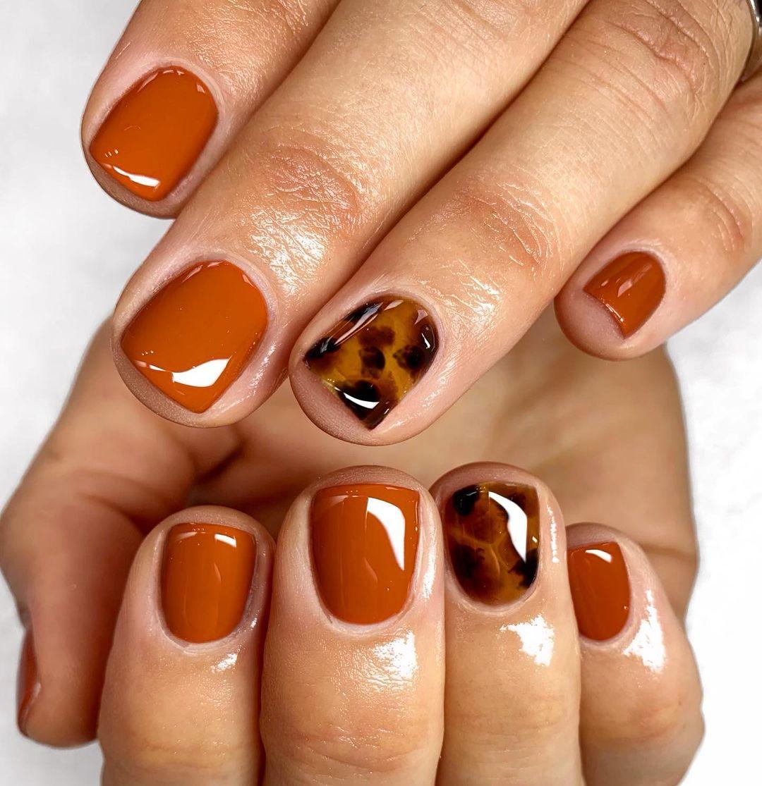Burnt orange gel nails with animal print