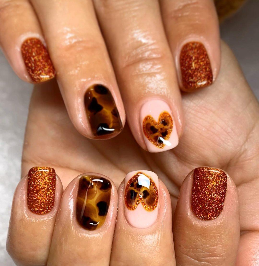 Short burnt orange glitter nails with tortoiseshell nail art