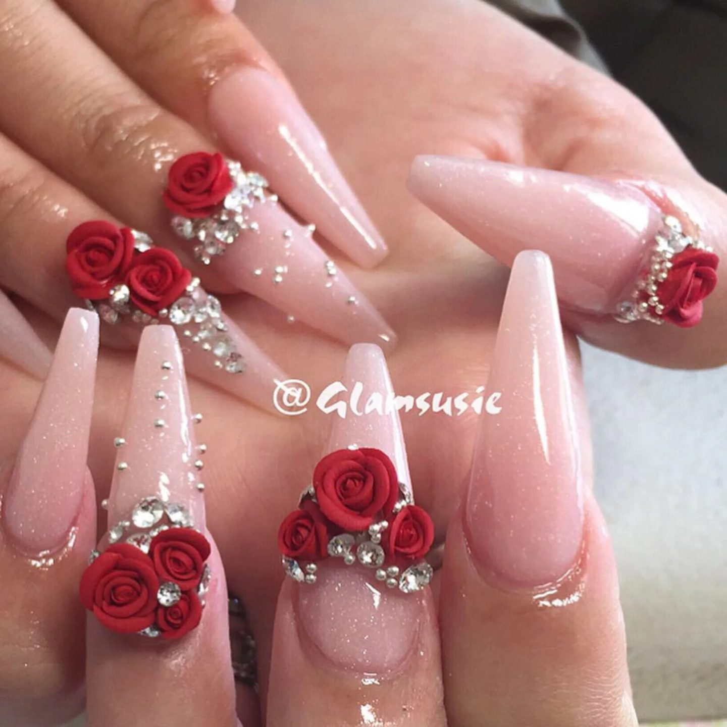 Cute nude stiletto nails with 3D red roses