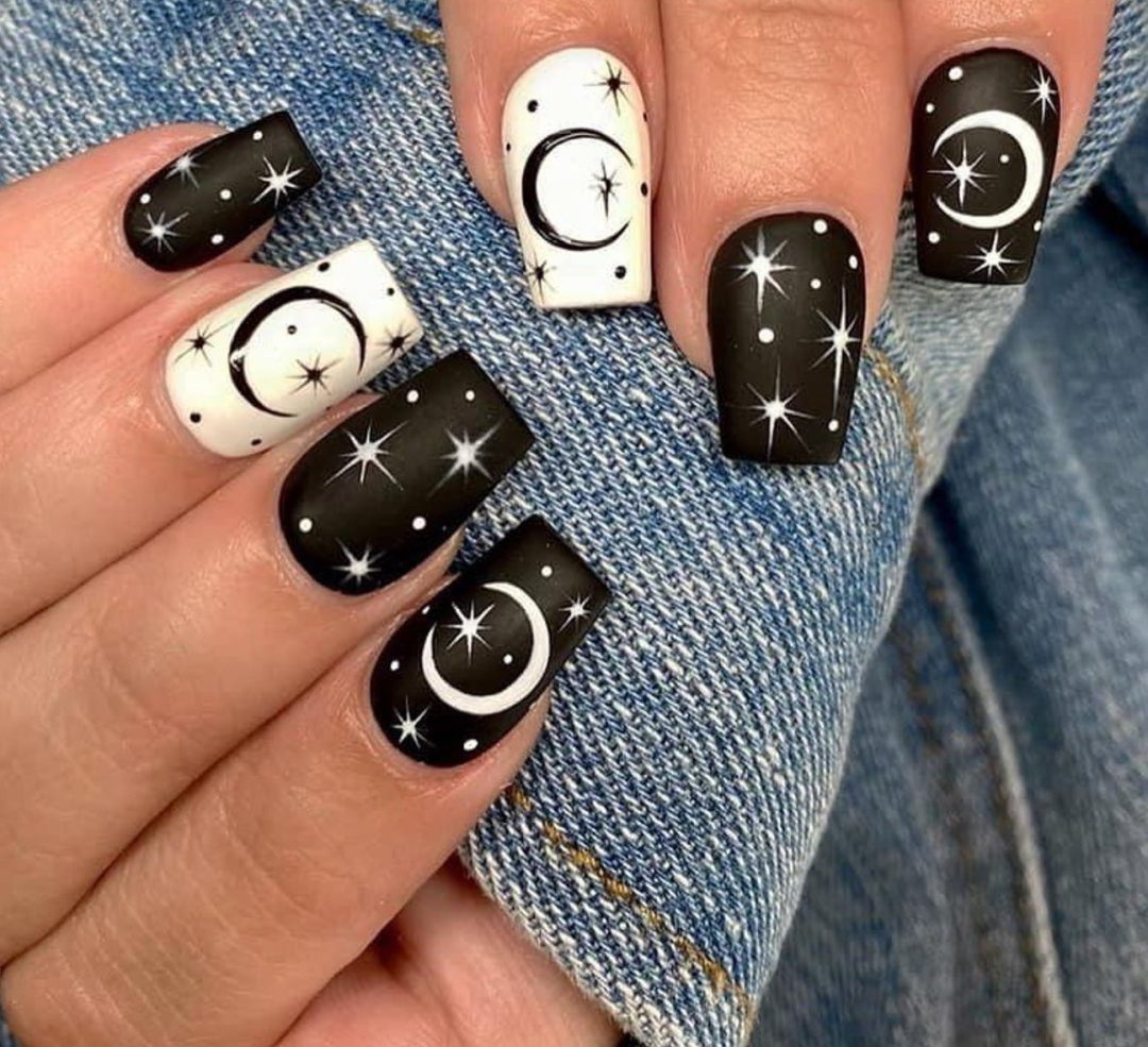 Matte black and white nails with moon and stars