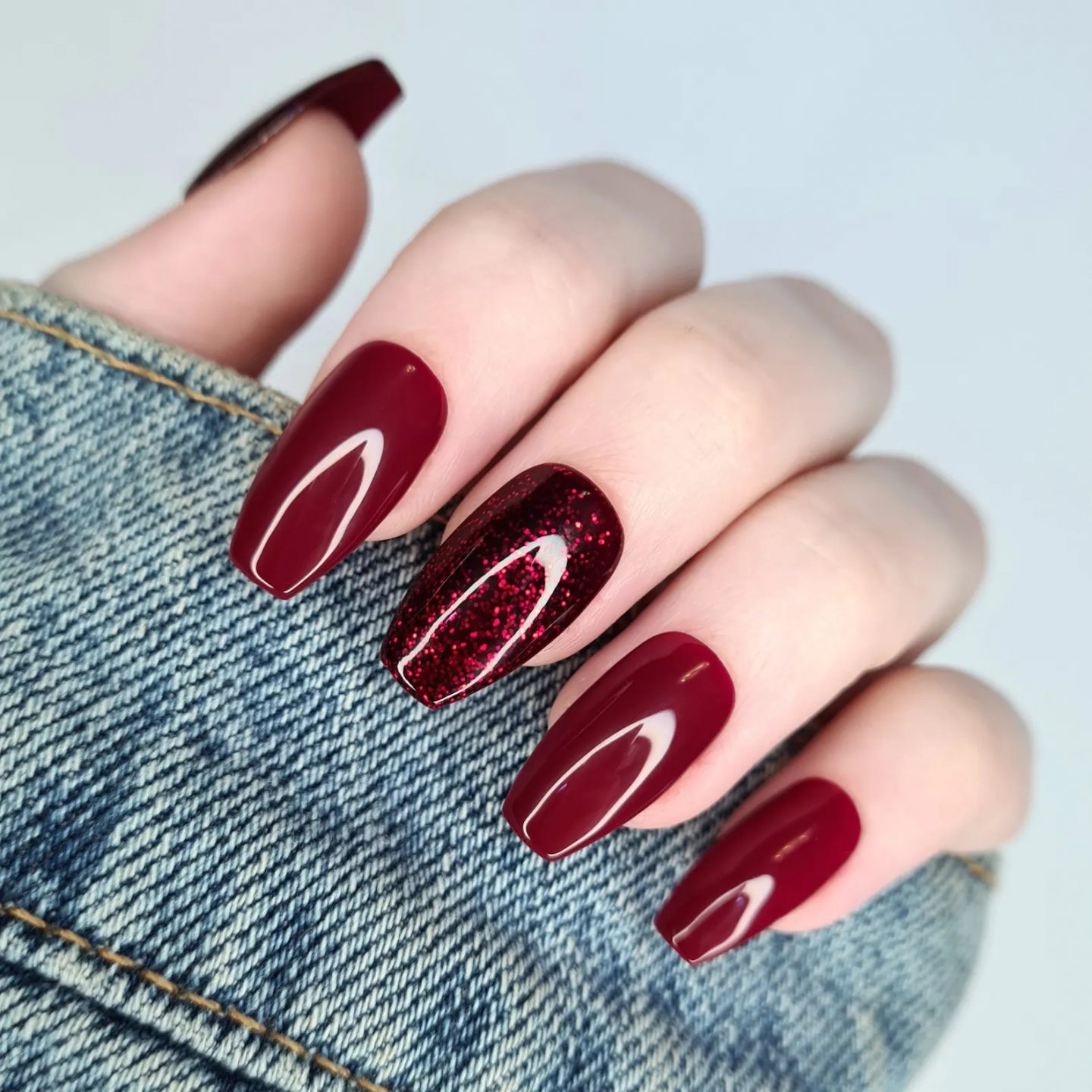 Short glossy wine red nails with glitter