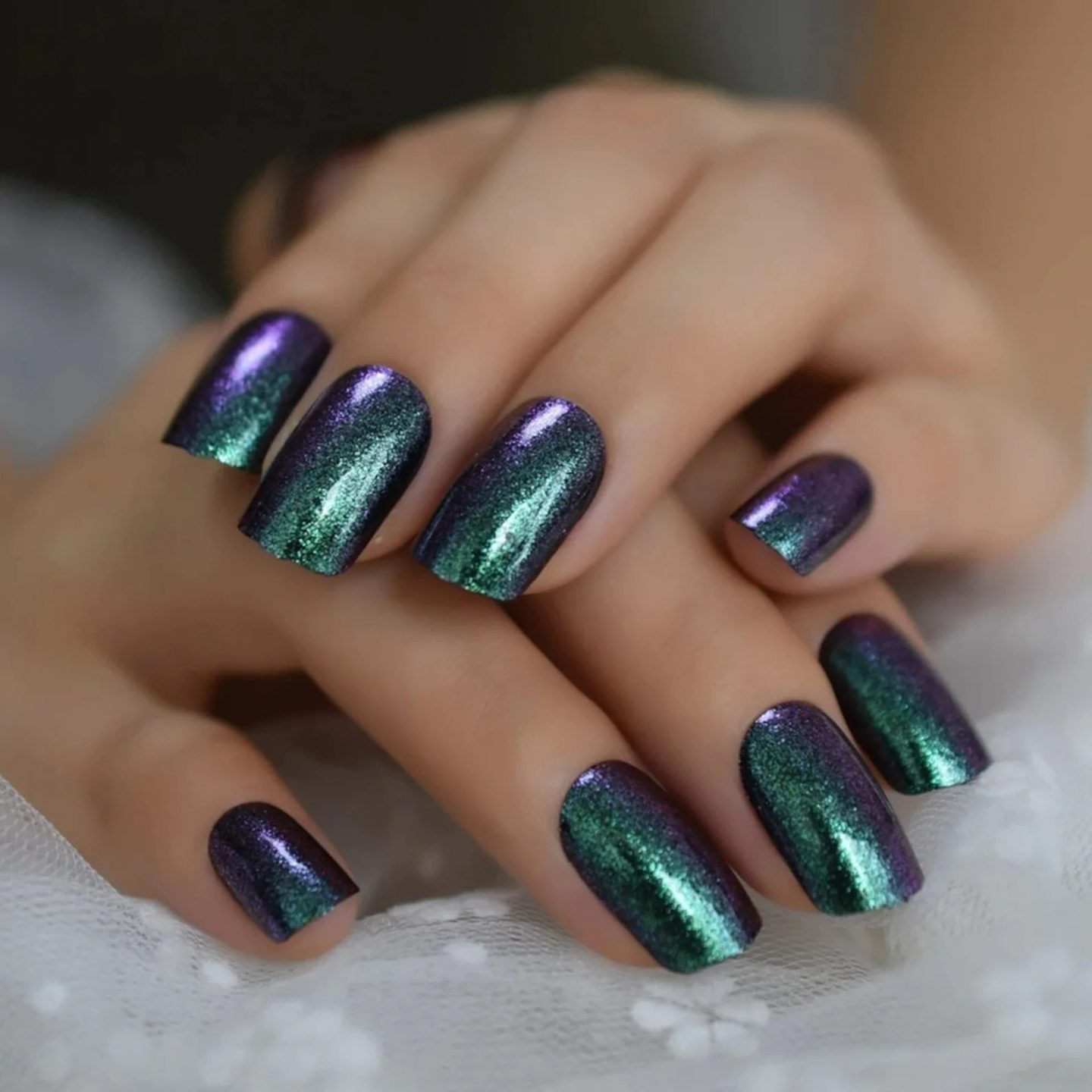 Short green and purple chrome nails with glitter