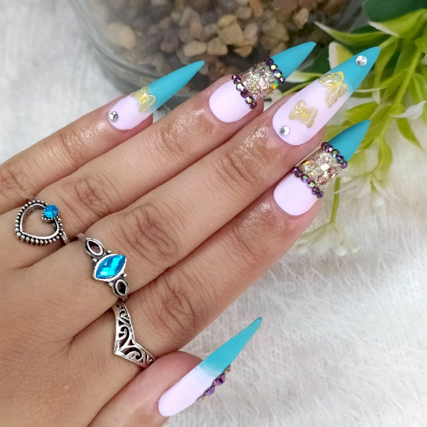 Long stiletto nails with turquoise French tips and rhinestones