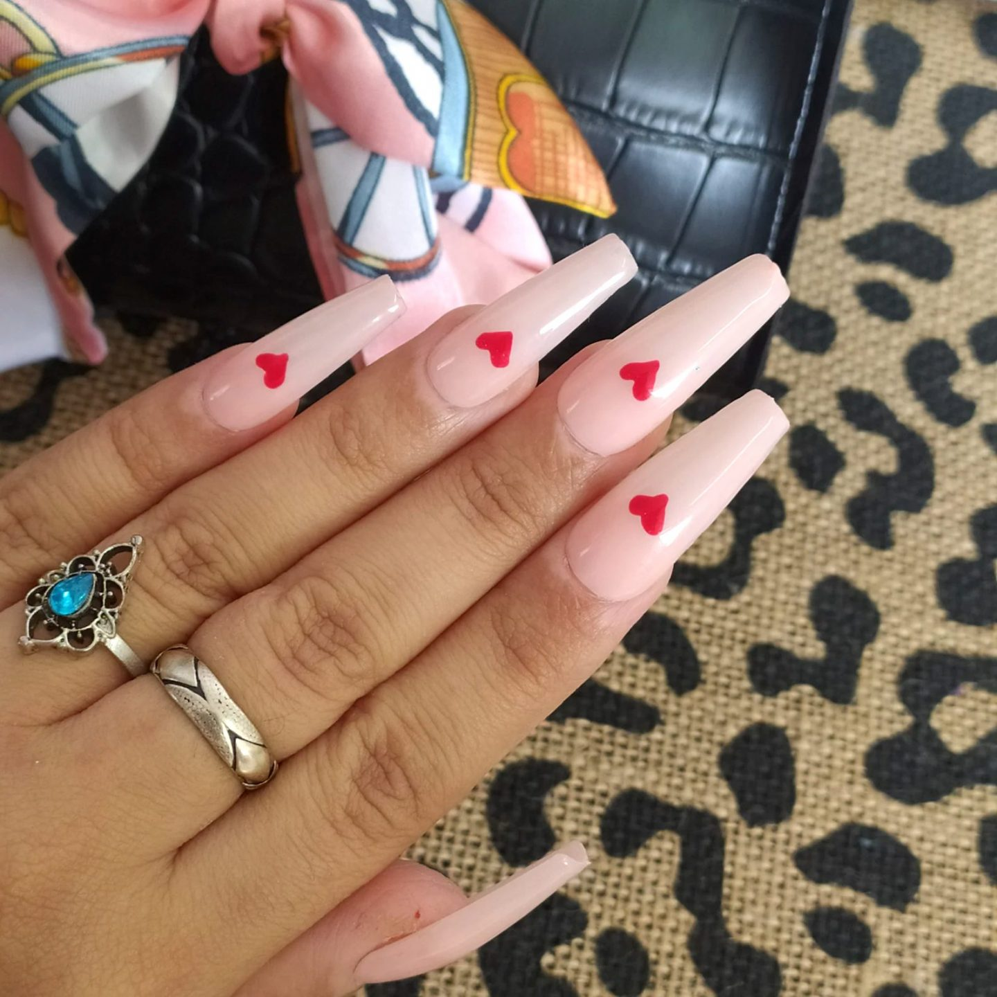 Cute light pink nails with small red hearts