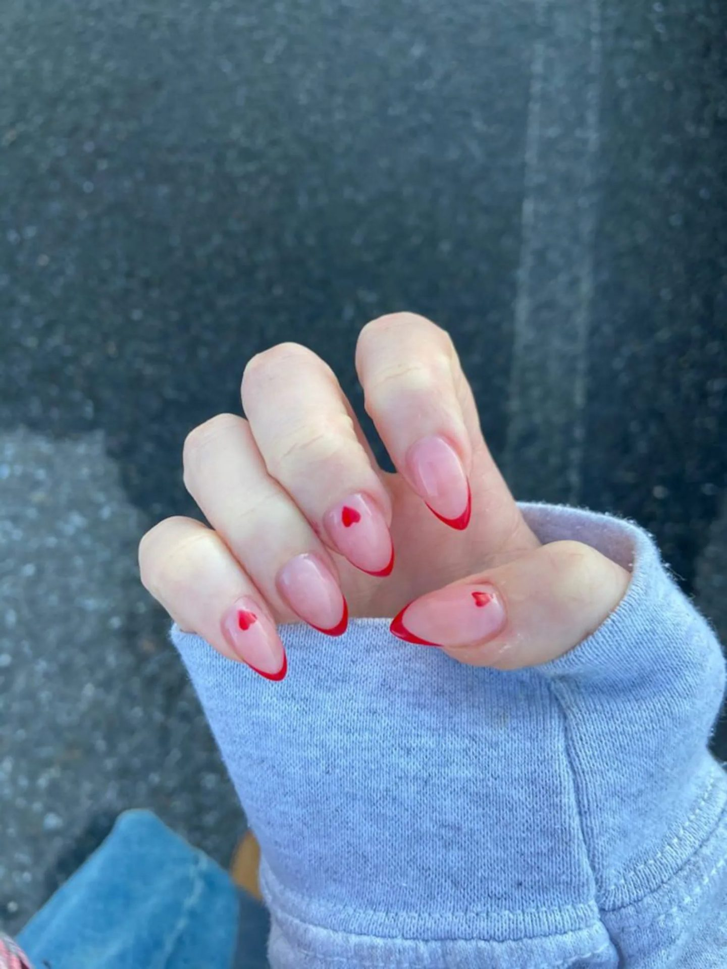 Red French tip nails with hearts in almond shape
