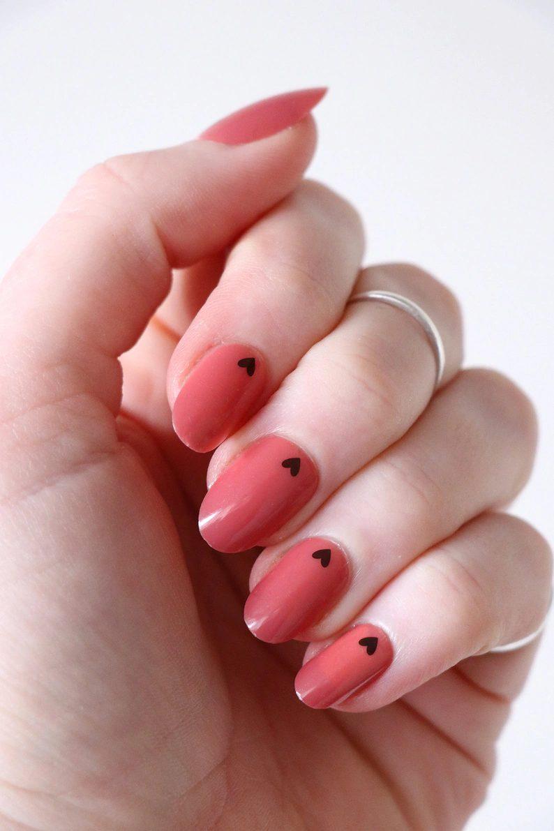 Cute short coral nails with tiny black hearts