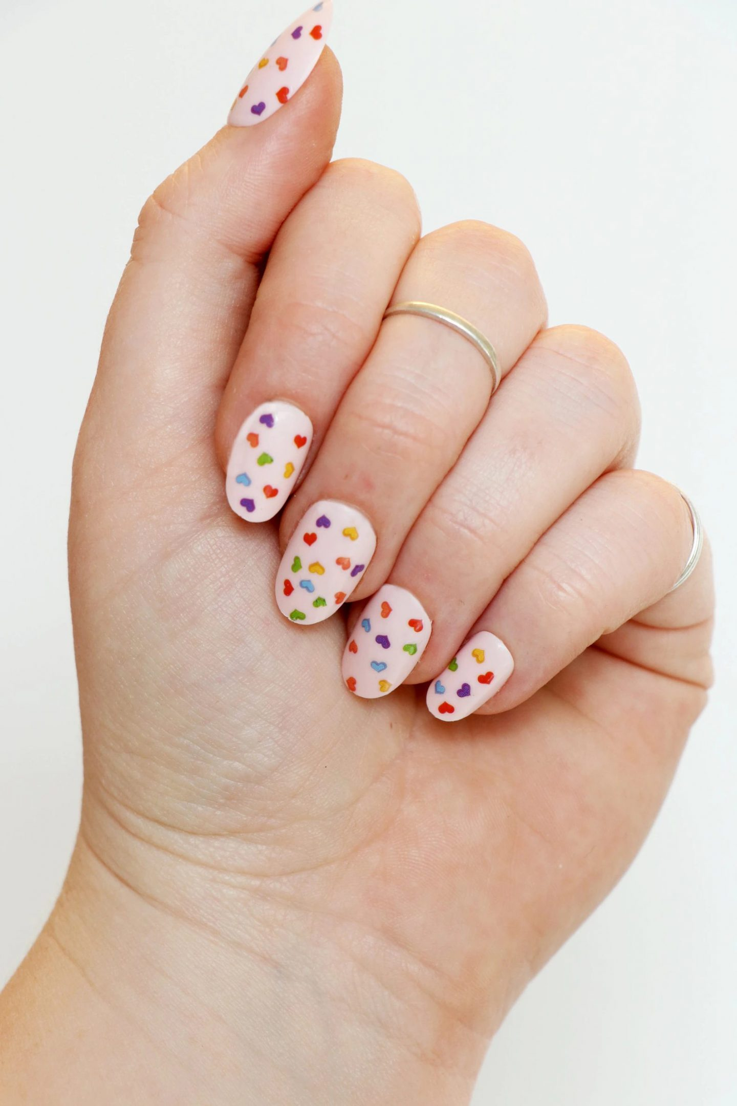 Cute short light pink nails with tiny rainbow hearts