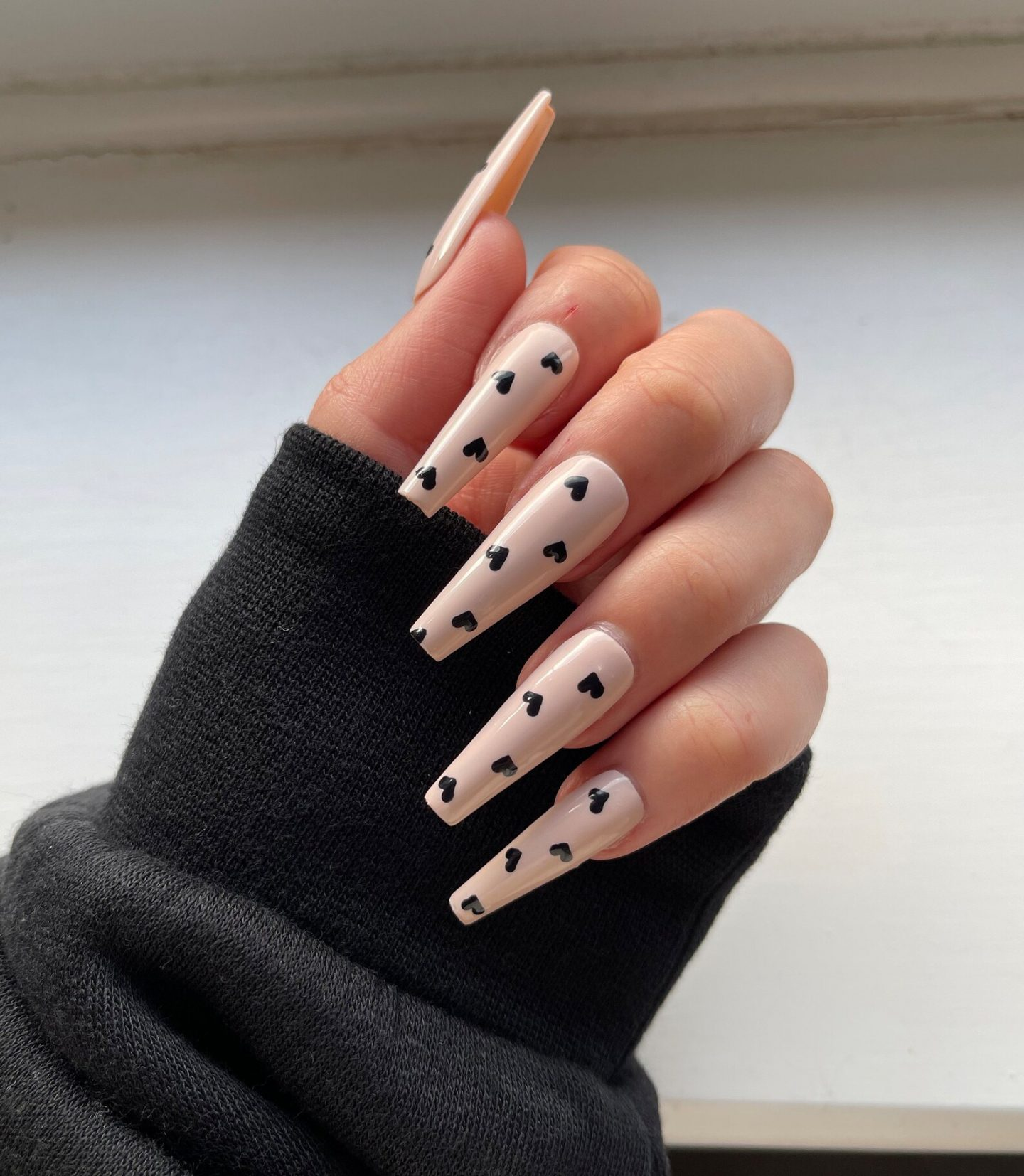 Long nude coffin nails with black hearts