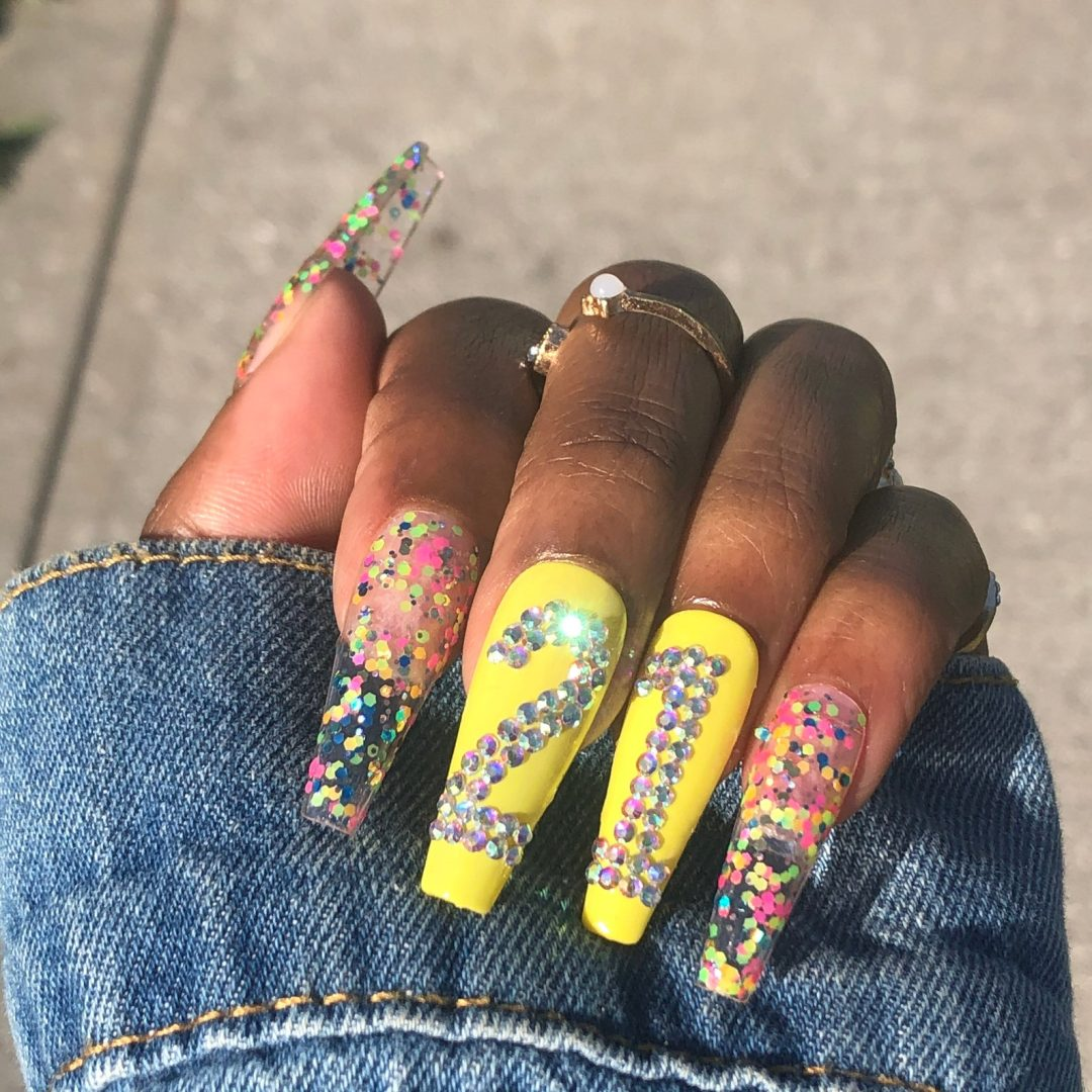Yellow and confetti nails with the number in rhinestones