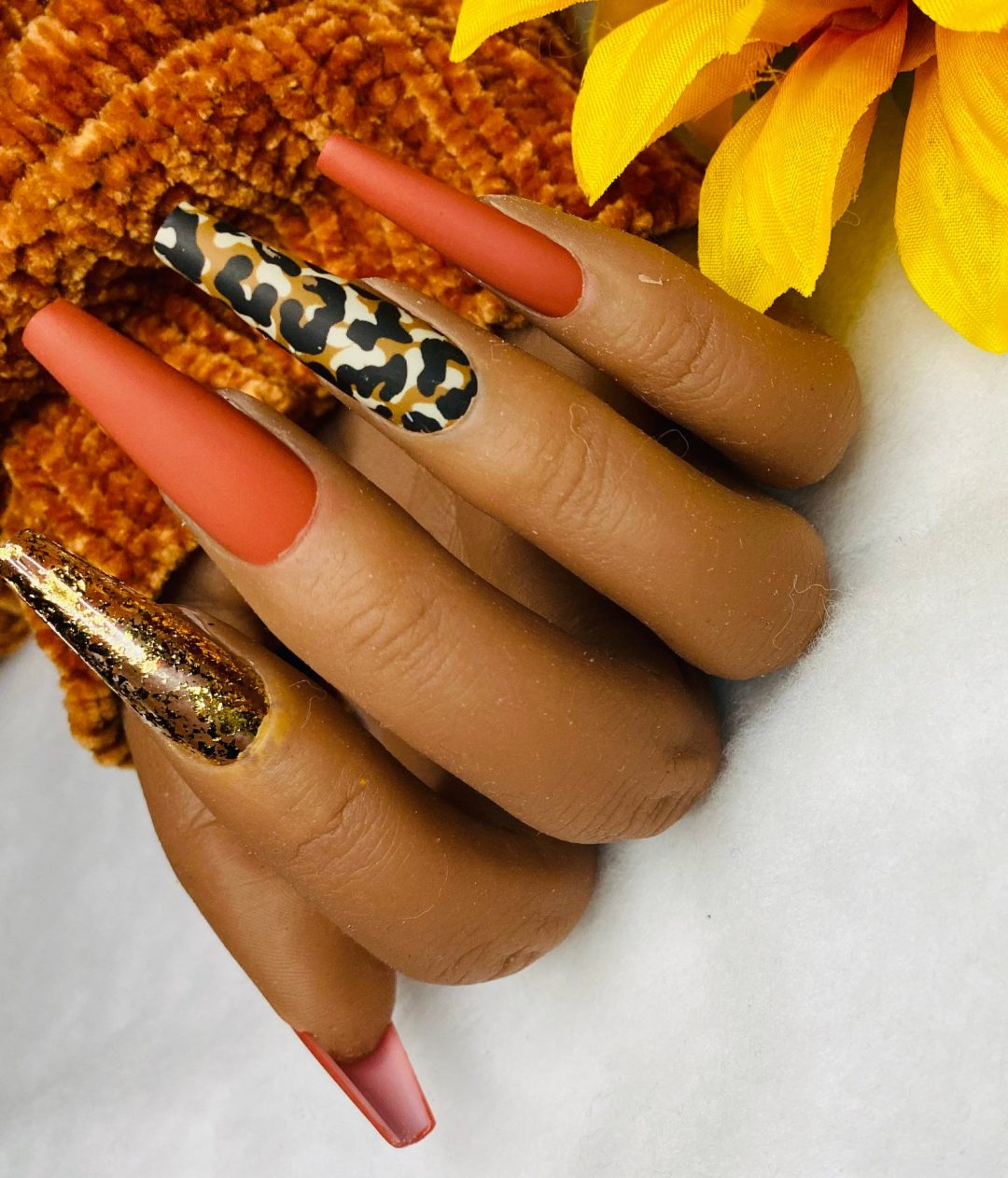 Matte rust colored nails with leopard print and gold glitter