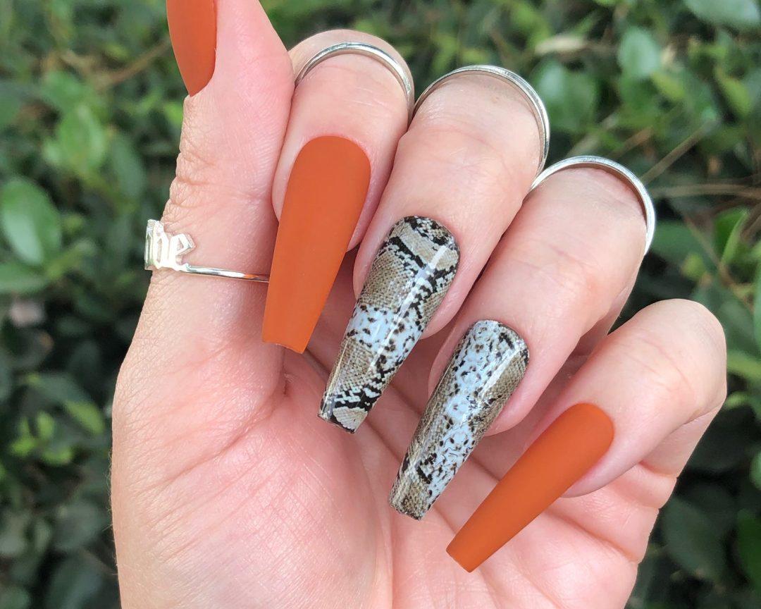 Matte burnt orange nails with snake print