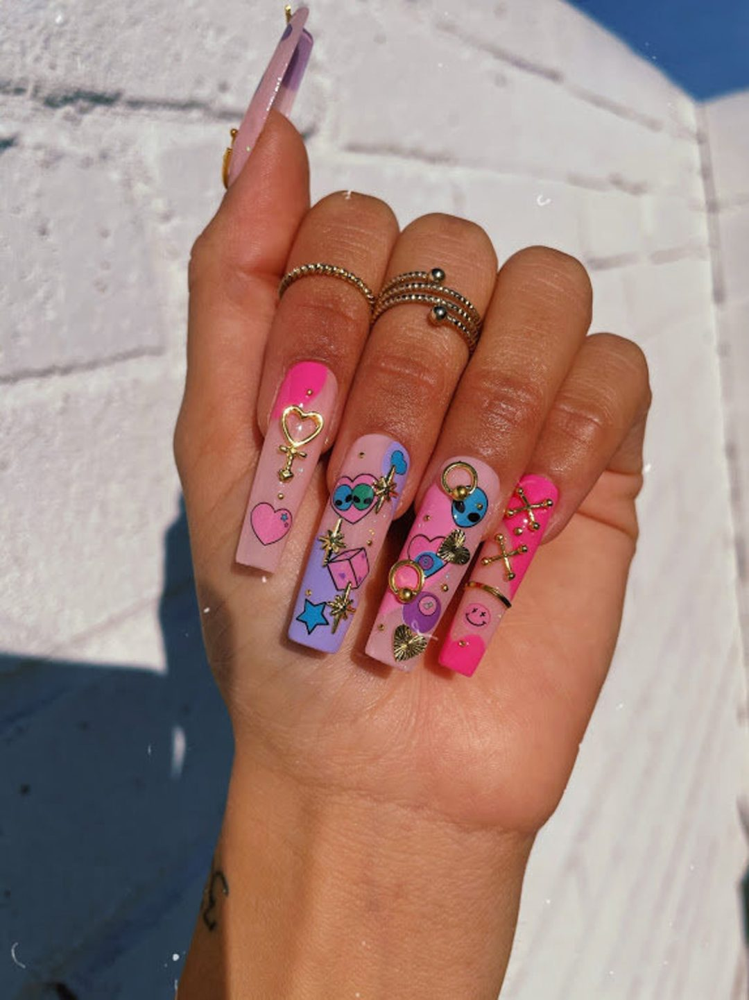 Cartoonish heart nails with aliens and gold decals