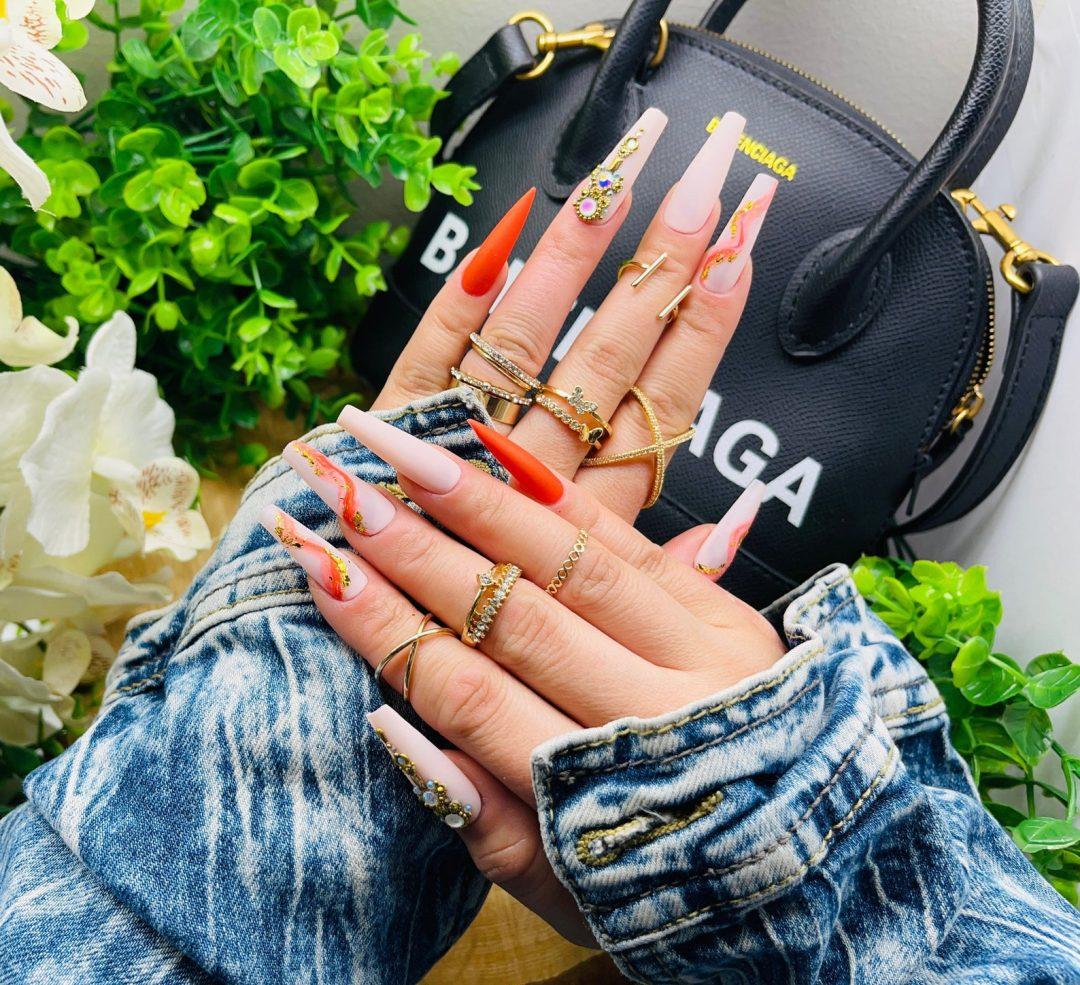 Burnt orange nails with nude nails and rhinestones