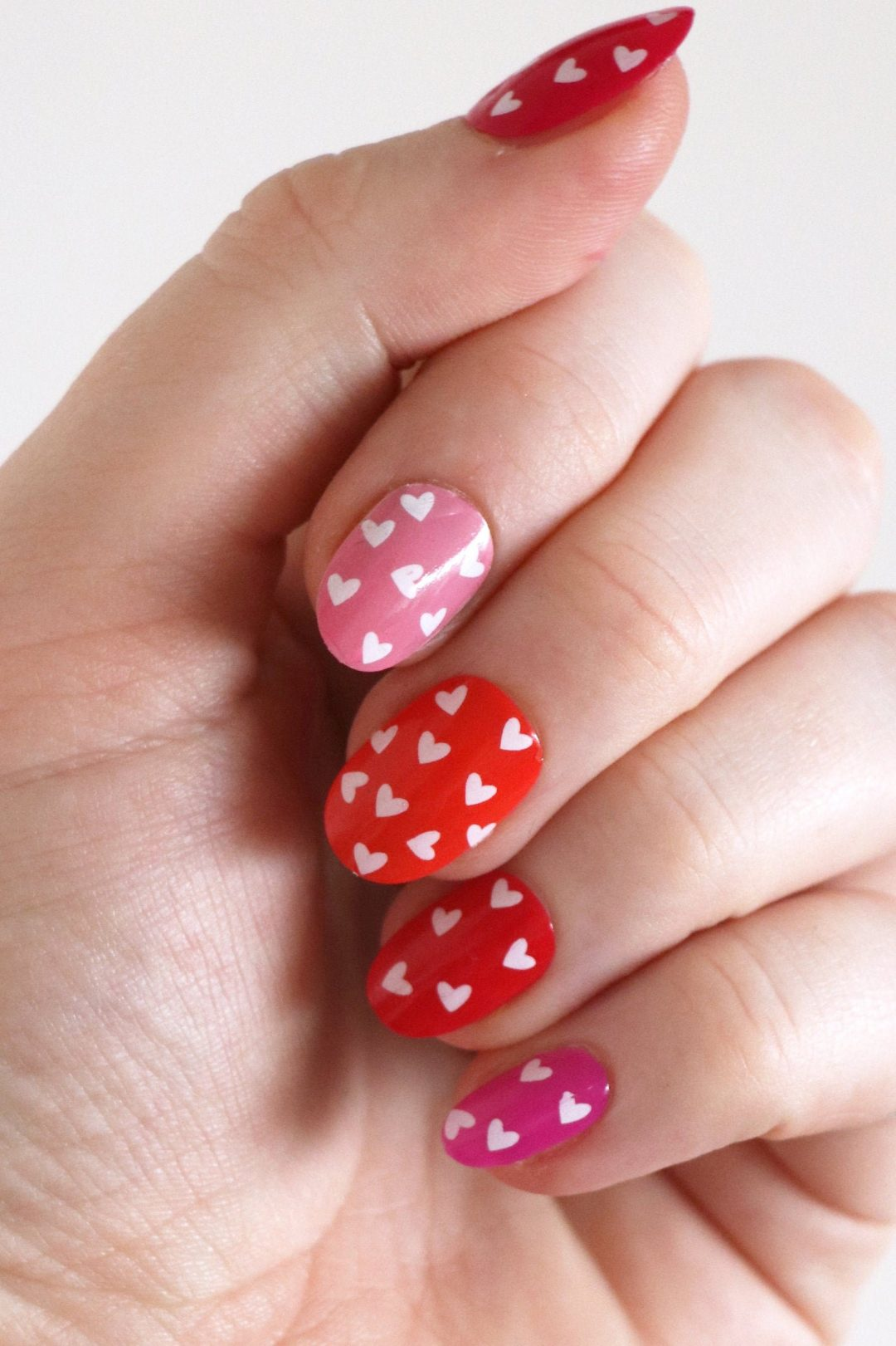 Pink and red nails with tiny heart decals