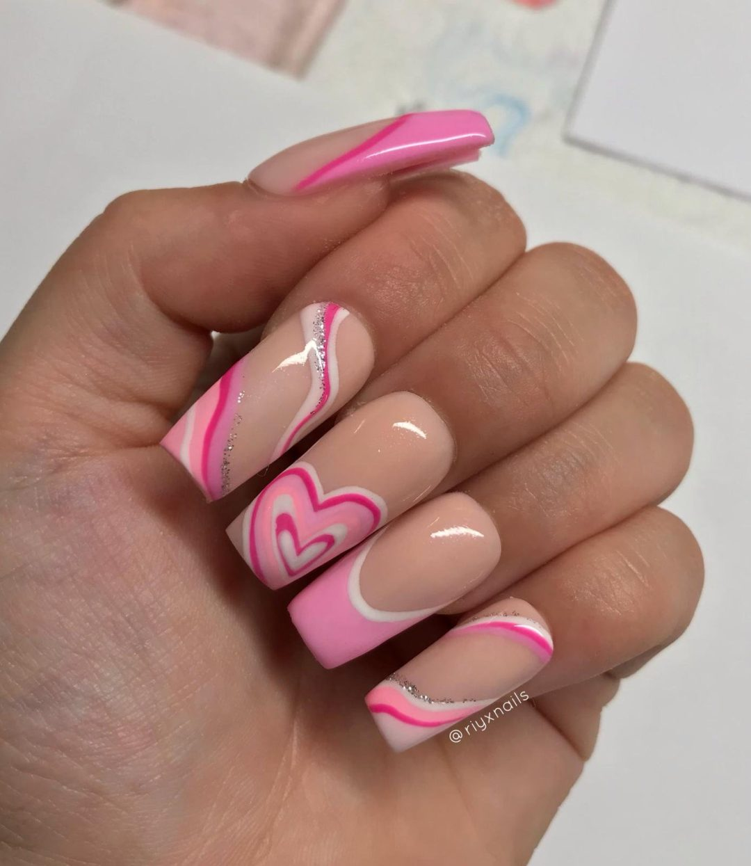 Swirly pink hearts on nude nails