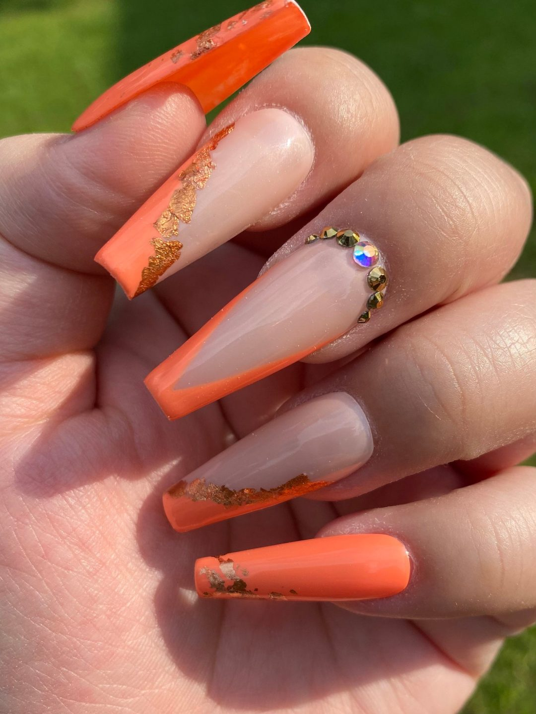 Burnt orange nails with nude and gold specks