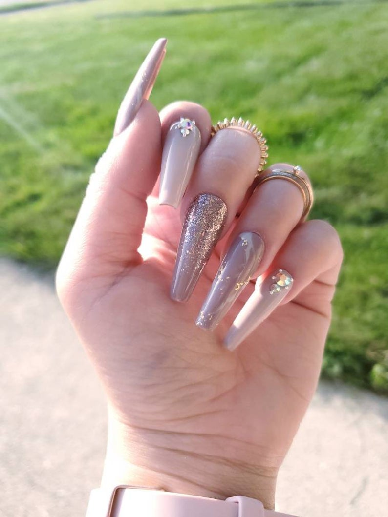 Light nude nails with glitter and rhinestones