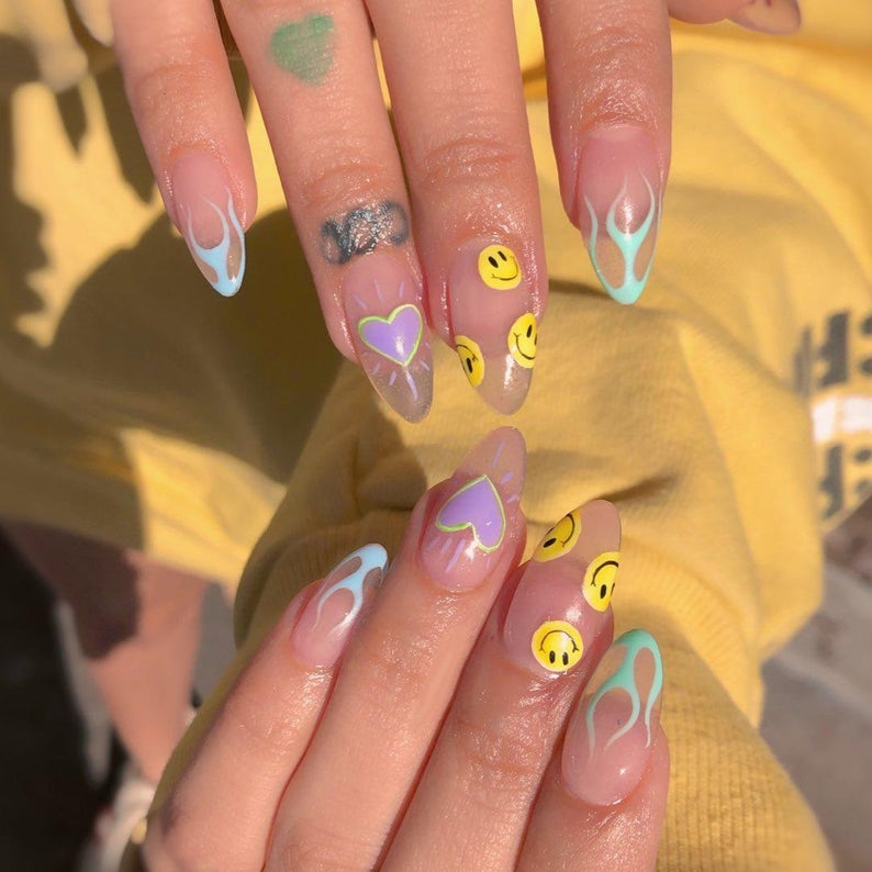Transparent smiley face nails with flames design