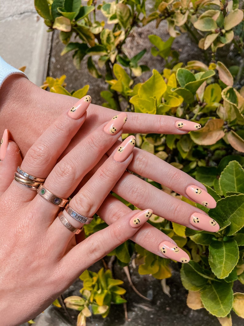 Nude polish with smiley face nails