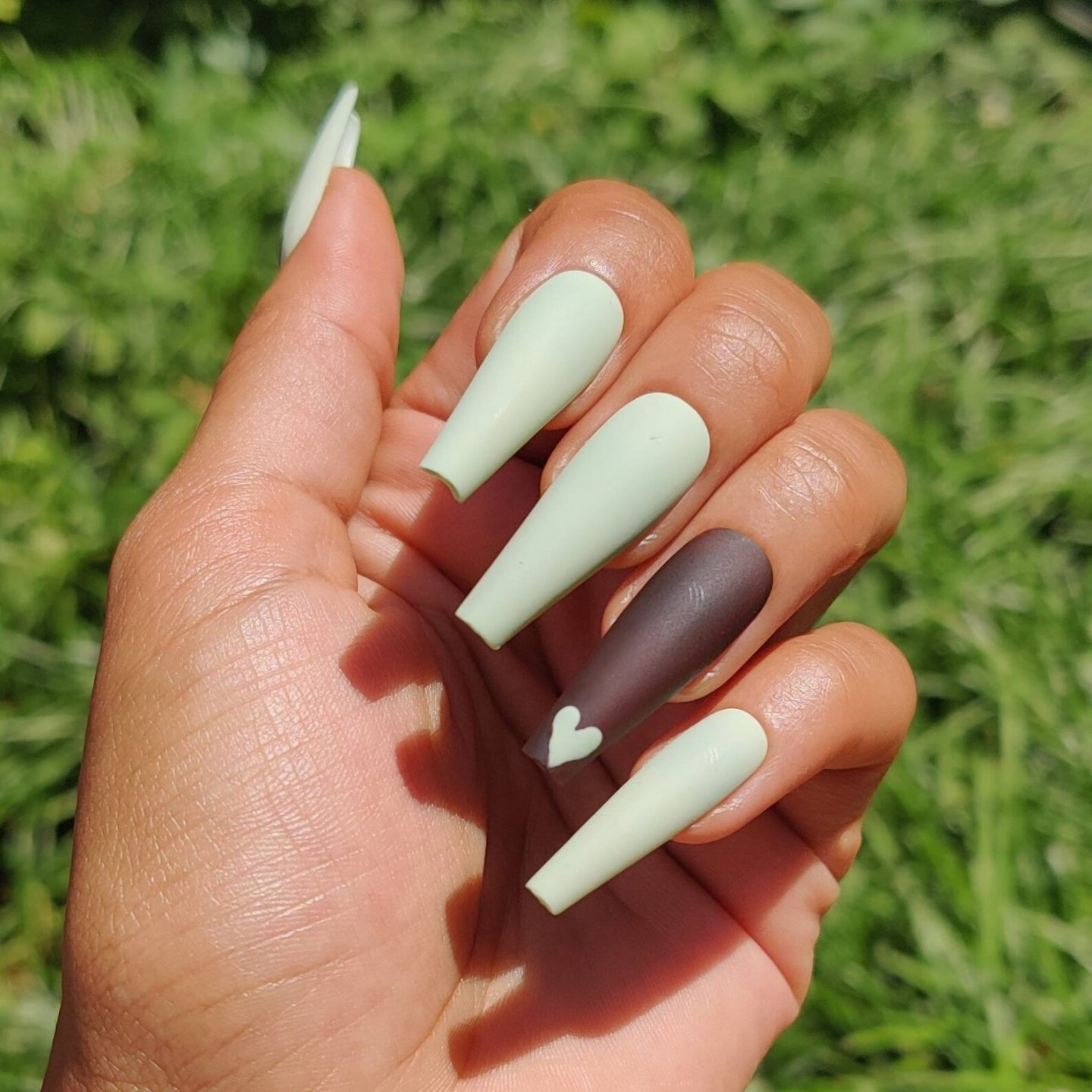 Long matte mint green nails with brown and heart nail art