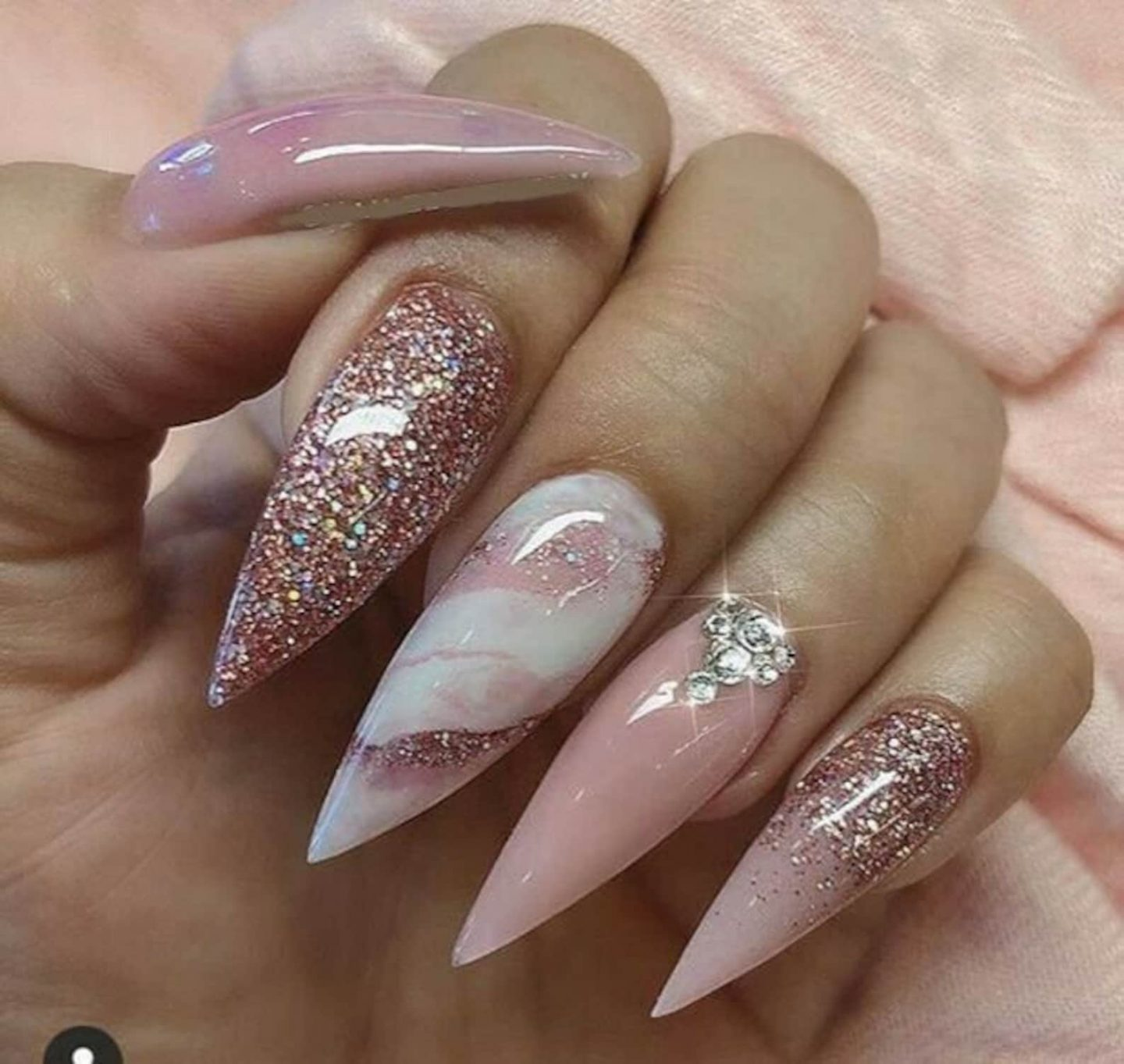 Long pink marble nails with rose gold glitter in stiletto shape