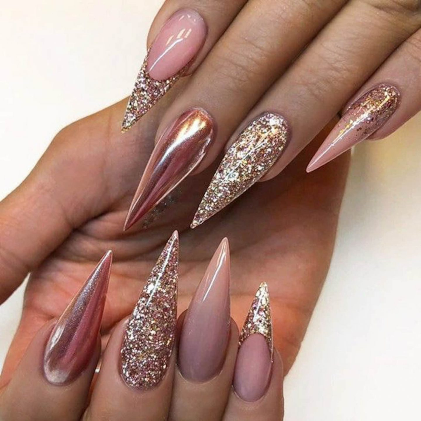 Nude stiletto nails with rose gold glitter