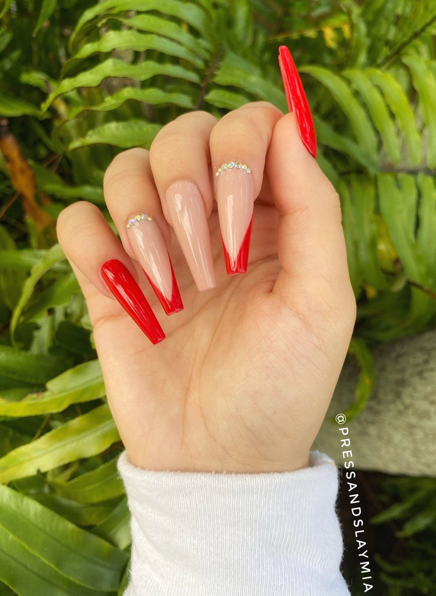 Nude and red French tip nails with rhinestones