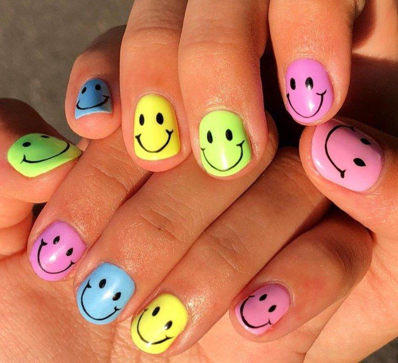 Short pastel rainbow smiley face nails