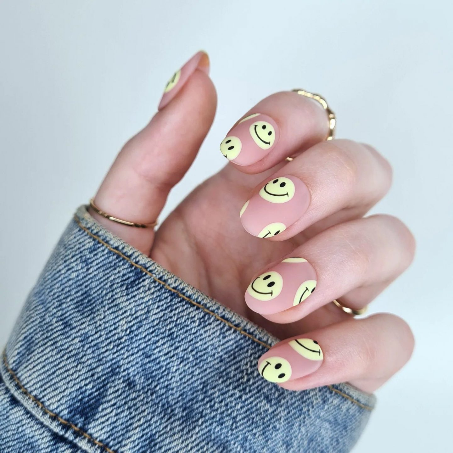 Nude nails with pastel yellow emojis