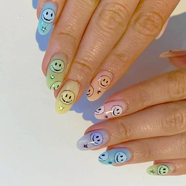 Pastel rainbow ombre nails with smiley nail art