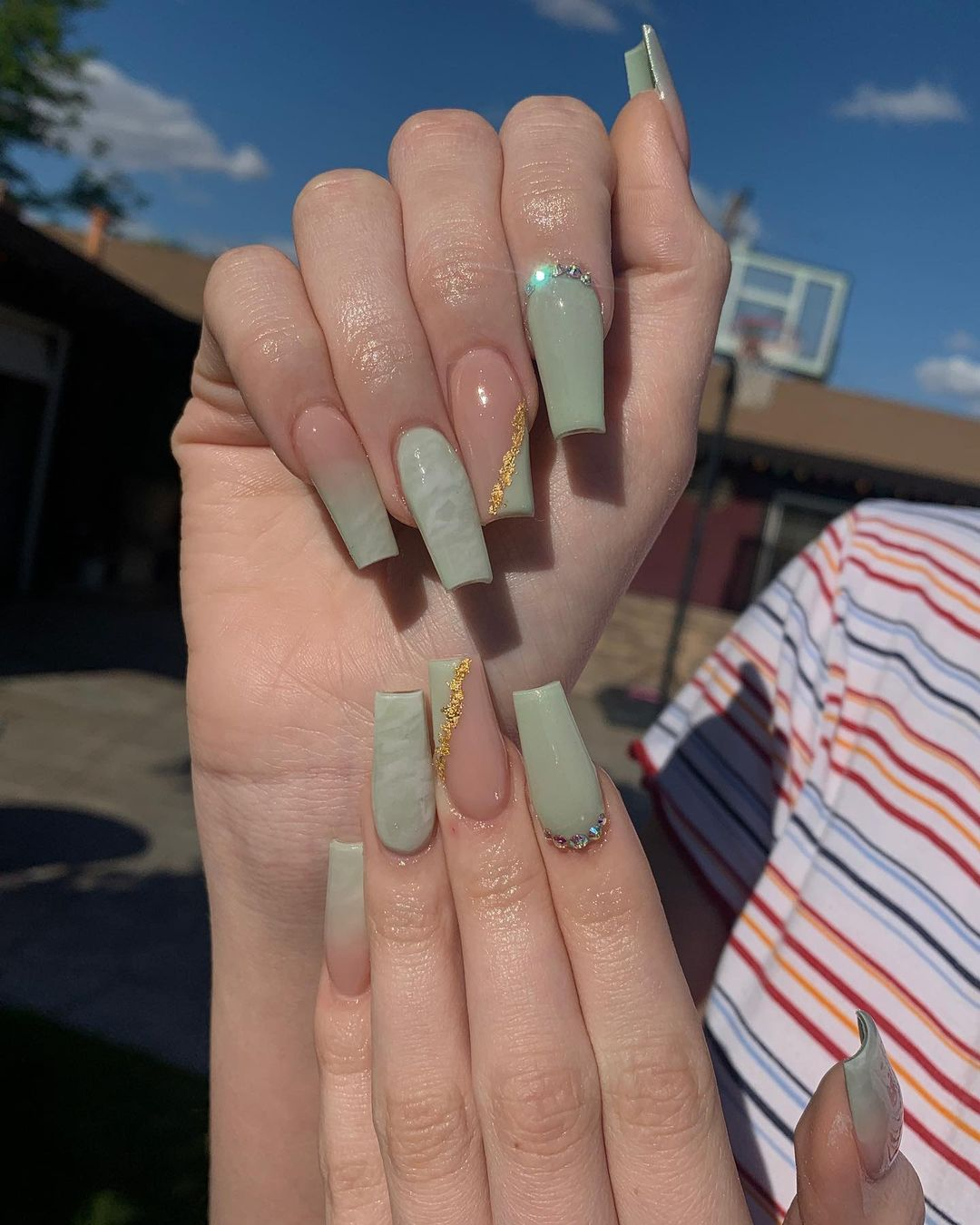 Sage green nails with gold designs